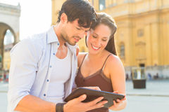 Young Tourists in city with tablet computer Royalty Free Stock Image