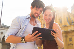 Young Tourists in city with tablet computer Royalty Free Stock Photo