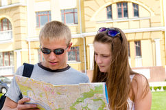 Young tourists consulting a map. Young couple of tourists consulting a map while sightseeing in an urban environment in summer sunshine Stock Image