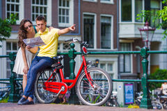 Young tourists couple looking at map with bikes in Royalty Free Stock Images