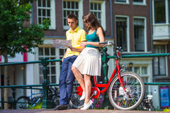 Young tourists couple looking at map with bikes in Royalty Free Stock Image
