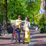 Young tourists couple looking at map with bikes in Stock Photography