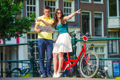 Young tourists couple looking at map with bikes in Stock Images