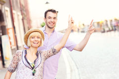 Young tourists hailing a taxi. A picture of a young happy couple hailing a taxi in a city Royalty Free Stock Image