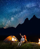 Young tourists man and woman looking at the shines starry sky at night. Happy couple sitting near tent and campfire Royalty Free Stock Image