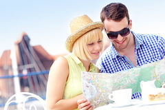 Young tourists with a map in a cafe Royalty Free Stock Photography