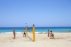 Young tourists playing volleyball on the sandy beach in Crete, G royalty free stock photography