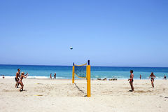 Young tourists playing volleyball on the sandy beach in Crete stock images