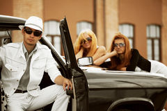 Young fashion people at the retro car outdoor Royalty Free Stock Image