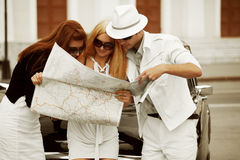 Young tourists with a road map at the retro car Stock Image