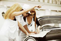 Young fashion people with road map next a retro car Stock Photography
