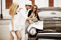 Young fashion people with a road map by retro car Stock Photos