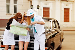 Young tourists with a road map against retro car Stock Images