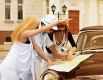 Young tourists with a road map against retro car Royalty Free Stock Images