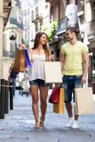 Young tourists in shopping tour. Happy men and long-haired women in casual clothes with shopping bags walking through street Royalty Free Stock Photos
