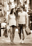 Young tourists in shopping tour. Happy men and long-haired women hunting after souvenirs in shopping tour Stock Photos
