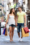 Young tourists in shopping tour. Happy men and long-haired women hunting after souvenirs in shopping tour Stock Photo