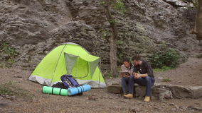 Young tourists with the tablet sitting near tent. stock video