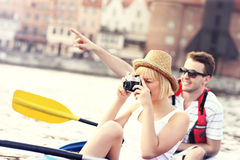 Young tourists taking pictures in a canoe. A picture of a young couple taking pictures in a canoe Stock Photo
