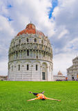 Young tourists vacationing in Pisa. Picture lying on the grass near the famous Leaning Tower in the old part of town, Italy stock images