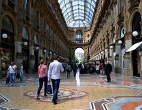 Young tourists walking along the Milan Vittorio Emanuele Gallery in summer. Royalty Free Stock Photography