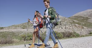 Young tourists walking down road. Two young tourists trekking in mountains and talking while walk with rocky hills on background stock footage