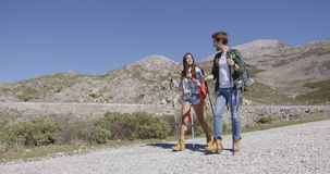 Young tourists walking down road Royalty Free Stock Photos