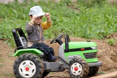 Young tractor driver. Young boy 2 years play in the garden with a toy tractor Stock Image