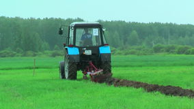 Young tractor operator plows the site in rain stock footage
