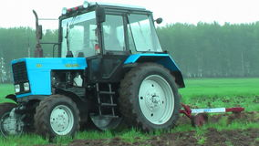 Young tractor operator plows the site in rain stock video