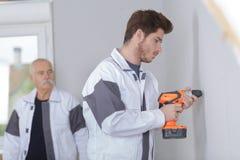 Young tradesman using cordless drill. Cordless royalty free stock image