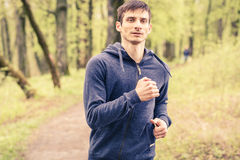Young trail runner man jogging in the morning park Stock Images