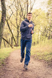Young trail runner man jogging in the morning park Royalty Free Stock Photography