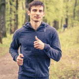 Young trail runner man jogging in the morning park Royalty Free Stock Photos