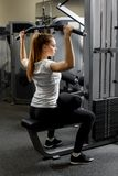 Young trained girl building biceps in a gym. Training for strength of the back muscles stock images