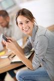 Young trainee in business class using smartphone Royalty Free Stock Photos