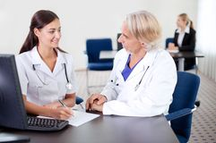 Young trainee sitting with a mature doctor Stock Photography