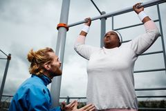 Yes you can. Young trainer encouraging plump female to try harder in doing pull-ups on bar Royalty Free Stock Photo