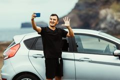 Young travel blogger man take selfie on the phone or wave on video translation for subscribers near car with ocean view. Car trip. royalty free stock image