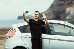 Young travel blogger man take selfie on the phone or wave on video translation for subscribers near car with ocean view. Car trip. stock images