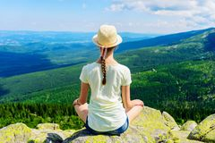 Young travel girl sitting on the rock mountain, relaxing Stock Photo