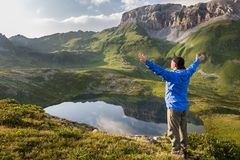 Hiker standing with raised hands near the beautiful mountain lake and enjoying view Royalty Free Stock Image