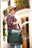 Young travel man holding bag and reading map. Portrait of a young travel man holding bag and reading map Royalty Free Stock Photo