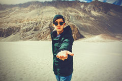 Young travel man lending a helping hand in outdoor mountain scene Royalty Free Stock Images