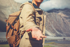 Young travel man lending a helping hand in outdoor mountain scenery Royalty Free Stock Photos