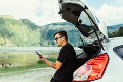 Young travel man in sunglasses sitting in car trunk chating on phone or check mail, surfing in internet while relax on beauty natu. Re landscape on background royalty free stock photo