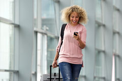 Young travel woman smiling with mobile phone and luggage Royalty Free Stock Image