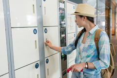 Young travel woman using the locker. In the airport royalty free stock images