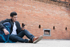 Young traveler, asian man wearing black jacket and blue jeans si. Young traveler, handsome asian man wearing black jacket and blue jeans sitting near old orange royalty free stock photo