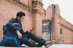Young traveler, asian man wearing black jacket and blue jeans si. Young traveler, handsome asian man wearing black jacket and blue jeans sitting near old orange Stock Image
